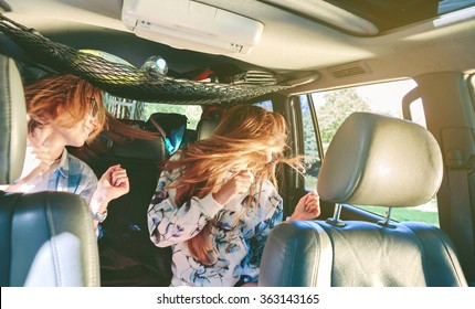 Two happy young women friends dancing and having fun inside of car in a road trip adventure. Female friendship and leisure time concept.