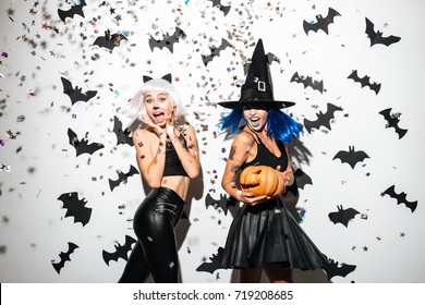 Two happy young women in leather halloween costumes posing with curved pumpkins over bats and confetti background