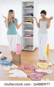 Two happy young women looking down at shopping bag and scatted clothes on floor at home