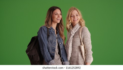 Two happy young women standing together looking around on green screen