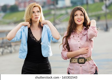 Two happy young women walking on the city street