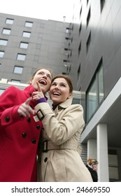 Two happy young women with winter coats, black building background