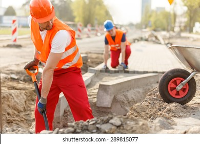 Two hard working builders in uniforms putting pavement