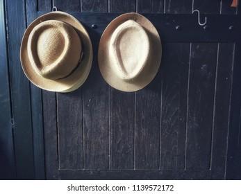 f461755726e Two hats hanging dark brown wooden doors.