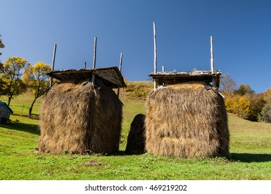 Two haystacks under the roof on the green meadow