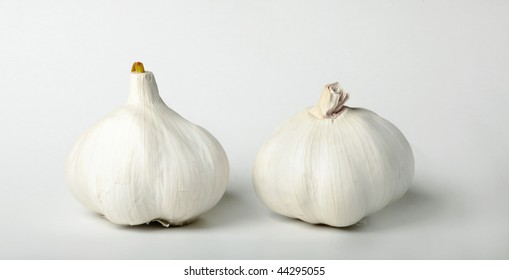 two heads of garlic on a gray background