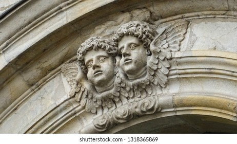 two heads of little angels with creepily bulging eyes on entrance to Cathedral Saint Jean (Besancon Cathedral of Saint John), church in Besancon city, Franche-Comte region, eastern France, Europe