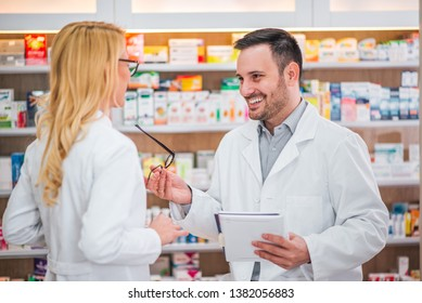 Two healthcare workers talking at drugstore.