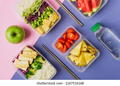 Two healthy asian-style plant-based lunch boxes knolled together on blue and pink background, flatlay