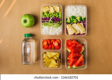 Two healthy asian-style vegan lunches in bento boxes with rice, fried tofu, edamame beans, broccoli and fruits, flatlay