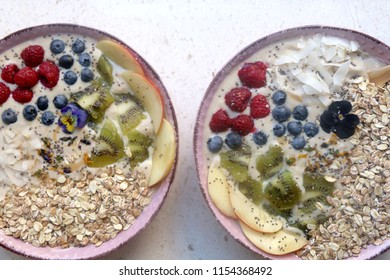 Two healthy smoothie bowls. Mango, peach and banana smoothie with various toppings (granola, coconut flakes, chia seeds, kiwi, blueberries, raspberries, peach). Top view.