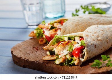 Two Healthy Tex-Mex tortilla wraps viewed from side on wooden cutting board, glasses in background