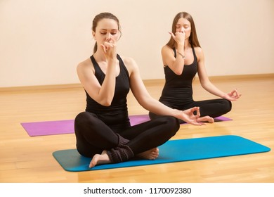 Two healthy women are practicing pranayama yoga. Instructor is teaching female student breathing exercise.