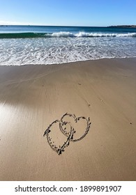 Two Heart is drawn on the sand. Beautiful view on the waves