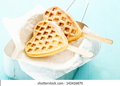 Two heart shaped Belgian waffles on a stick inside a tin can a a paper wrap, sprinkled with cinnamon and sugar