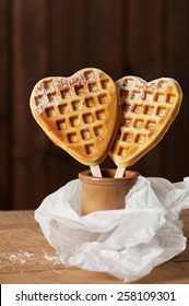Two heart shaped golden waffles on a stick in a ceramic pot.