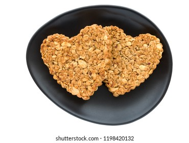 Two heart shaped oat and peanut cookies (flapjack biscuits) on oval black plate on white background