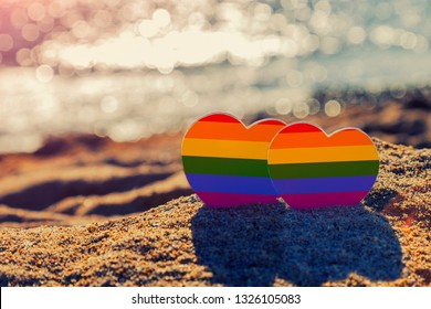Two hearts of the color of the gay flag on sand on the coast of the sea. Romantic trip gay honeymoon same-sex couple. LGBT concept. Minority sex. Heart sign with gay pride LGBT rainbow flag wristband.
