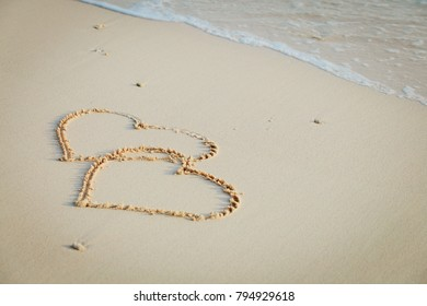 two hearts drawn on sand beach
