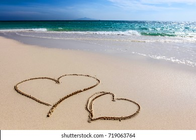 Two hearts drawn on white sandy beach and sea