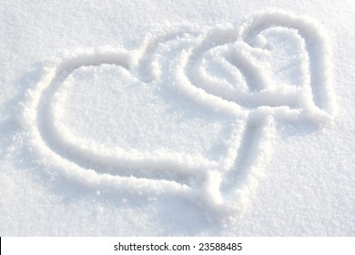 Two hearts drawn on white-blue snow
