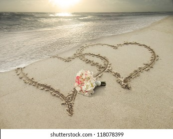 Two hearts drawn in sand at the beach. Wedding concept.
