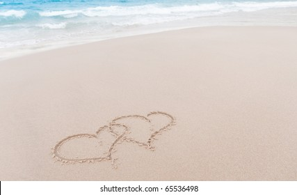 Two hearts drawn in the sand at the beach