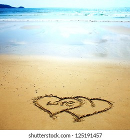 Two hearts drawn in the sand on the beach. Romantic design element.