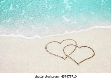 Two hearts handwritten on sand of tropical beach, background