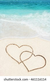 two hearts handwritten on sandy beach with azure ocean wave on background
