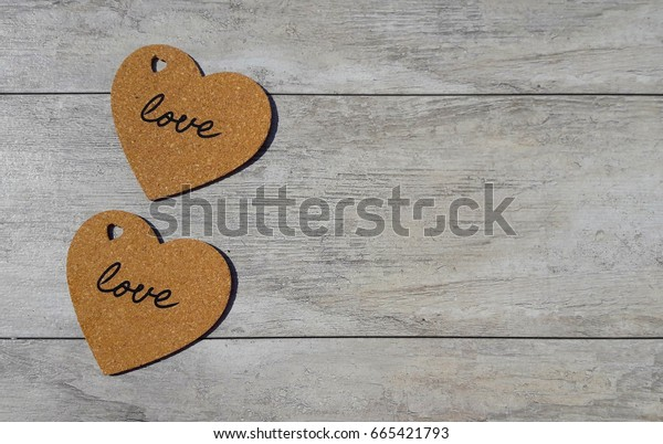 Two hearts with a love inscription on a wooden surface