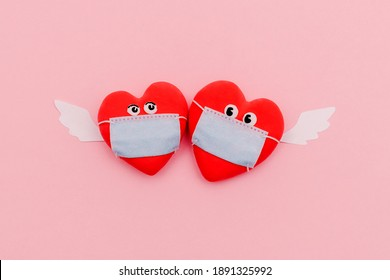 Two hearts in protective masks with eyes and angel wings on a pink background. Valentine's Day and coronavirus pandemic concept.Flat lay, top view.