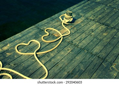 Two hearts from a rough rope on a textural wooden pier against the sea. Two hearts from a sea rope. Valentine's Day card