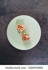 Two heart-shaped Welsh cakes, with sugar and raisins, on a green plate