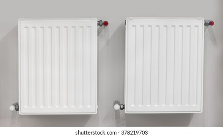 Two heating radiators with thermostat. Connection is done through the wall