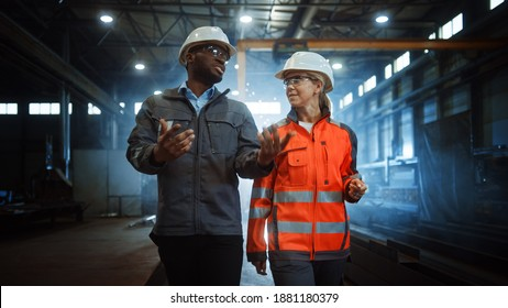 Two Heavy Industry Engineers in Hard Hats Walk in Steel Metal Manufacturing Factory and Have a Discussion. Black African American Industrial Specialist Talk to Female Technician in Manufacture.