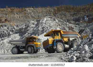 Two heavy quarry trucks inside a quarry for limestone mining, close-up. Heavy equipment. Mining industry.