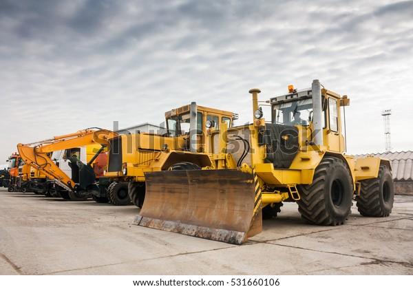 Zwei schwere Traktoren, ein Bagger und andere Baumaschinen