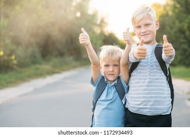 Two heerful blondy boys gives a thumbs-up. Schoolboys smiling and happy.