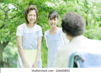 Two helpers greeting senior woman
