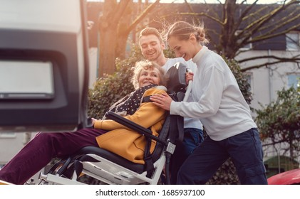 Two helpers picking up disabled senior woman in wheelchair for transport