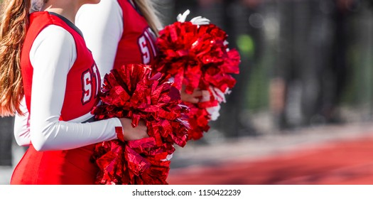 Two high school cheeleaders with red and white pom poms at a football game in autumn.