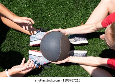 Two high school girls are passing a medicine ball while doing situps on a green turf field.