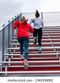 Two high school girls are running up bleachers as part of their warm up for track and field practice.