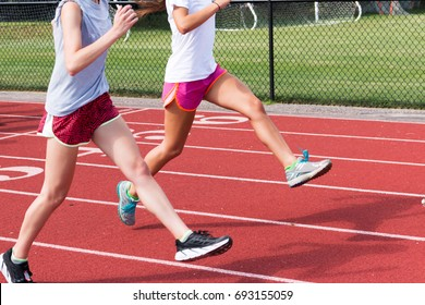 Two high school track and field athletes perform straight leg bounding on a red track at practice outside