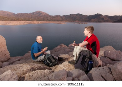 Two Hikers with Backpacks Eating Snacks