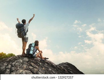 Two hikers with backpacks enjoying view from top of a mountain