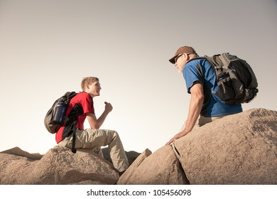 Two Hikers with Backpacks Having a Snack Break