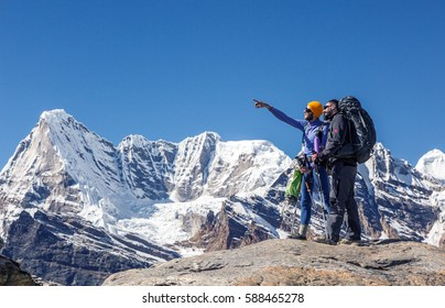 Two Hikers with Backpacks and other climbing Gear staying on top of Rock and discussing the Rout and pointing in high Mountains of Himalaya range