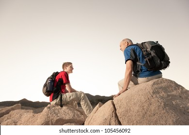Two Hikers with Backpacks Relaxing on Boulders